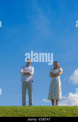 a couple with a conflict on a meadow - Stock Photo