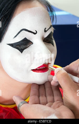 Pierrot clown woman getting her face painted - Stock Photo