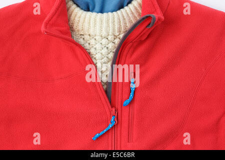 Person wearing a red fleece jacket with zip open over an Arran sweater for warm winter clothing. England, UK, Britain - Stock Photo