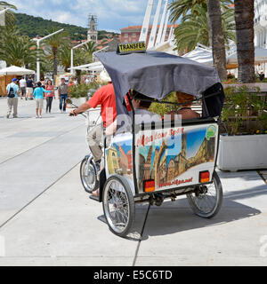 Couple riding in a rickshaw along the waterfront promenade in Split town centre on a sightseeing tour - Stock Photo