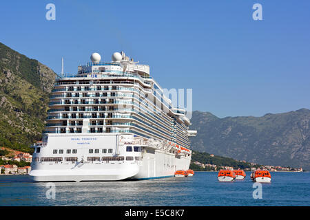 Regal Princess cruise liner anchored close to Kotor Town with ships lifeboat tenders alongside to ferry passengers - Stock Photo