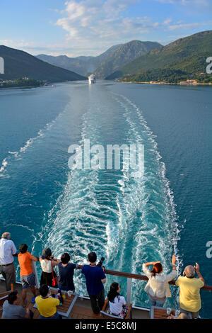 Stern of cruise ship liner passengers view ships wake & landscape departing Verige Strait in Kotor Bay Montenegro - Stock Photo