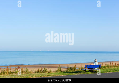 Man sitting on a bench on the seafront at Thornton Cleveleys in the early morning, North Blackpool, Lancashire, - Stock Photo
