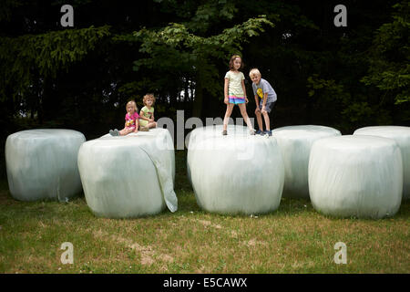Group of children playing on bales of straw looks like giant teeth, summer time - Stock Photo
