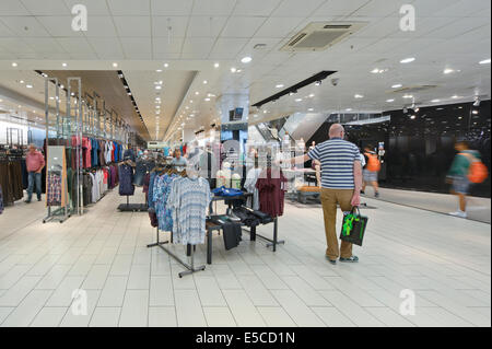 Interior of Next flagship store in the Arndale in Manchester city centre, including a man looking bored. (Editorial - Stock Photo