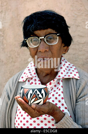 An elderly Native American woman holds a piece of prized pottery that she has handmade in Acoma Pueblo, a remote - Stock Photo