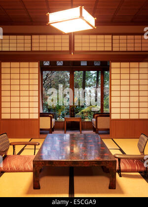 Tea table chabudai and zaisu chairs at traditional Japanese ryokan room with garden view in Gero, Japan - Stock Photo