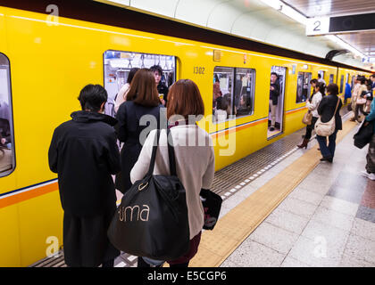 People at a subway station platform entering a train. Tokyo Metro, Tokyo, Japan. - Stock Photo