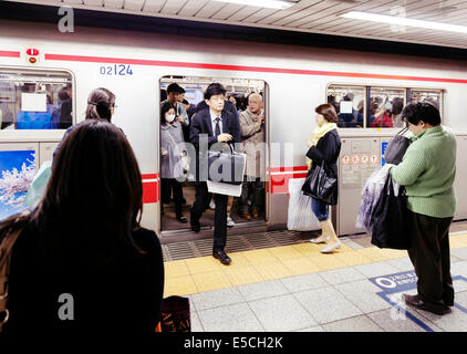 People getting off a subway train in Tokyo, Japan. - Stock Photo