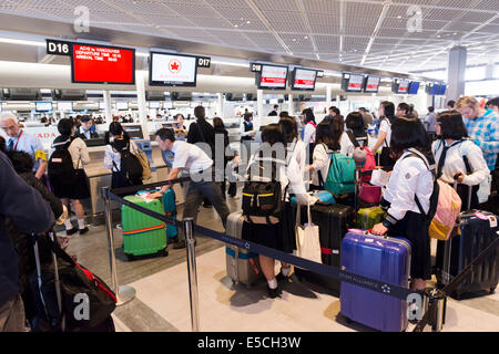 Japanese schoolgirls lined up at Air Canada check-in counter of Narita International Airport in Japan - Stock Photo
