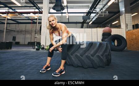 Beautiful and strong young woman sitting on a big tire after her exercise. Woman taking break after crossfit workout - Stock Photo