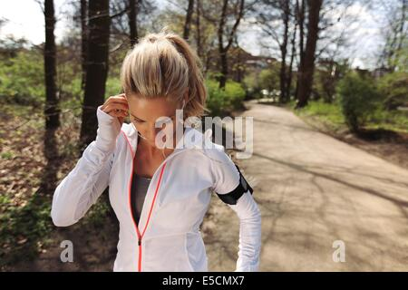 Image of pretty young blonde wearing earphones to listen music before starting her running workout. Fit female athlete - Stock Photo