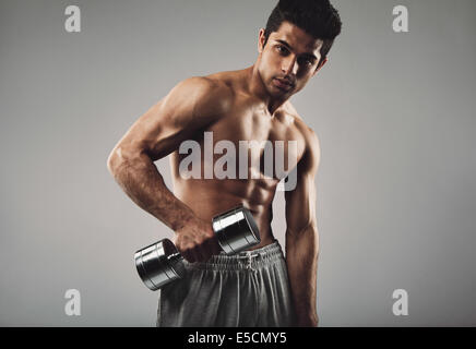 Portrait of hispanic young man working out with heavy dumbbell on grey background. Shirtless muscular man doing - Stock Photo