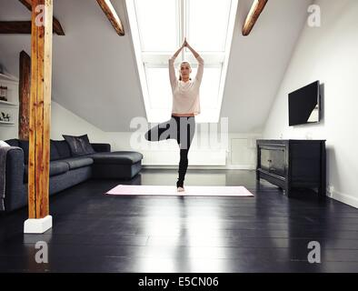 Full length image of fit young woman standing on one leg and meditating in her living room. Caucasian female doing - Stock Photo