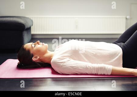 Image of fit young woman relaxing on yoga mat. Female lying on floor - Savasana - Stock Photo