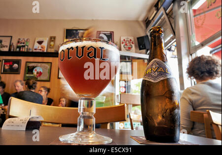 Orval Trappist Belgian Ale bottle and glass on a table opposite in a typical Belgian tavern - Stock Photo