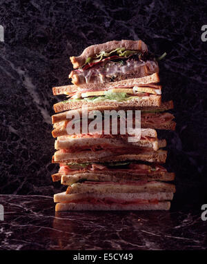 A stack of sandwiches one on top of the other, against a green and purple marble background. - Stock Photo