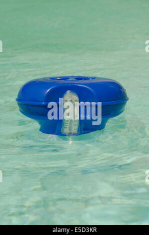 Chlorine container in pool with build in thermometer. - Stock Photo