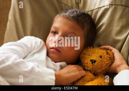 child feeling sick in bed - Stock Photo