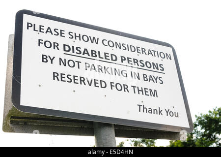 Sign asking drivers to show consideration for disabled persons by not parking in bays reserved for them - Stock Photo