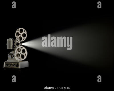 A three quarter angle shot of an old style film projector shot against a dark background - Stock Photo