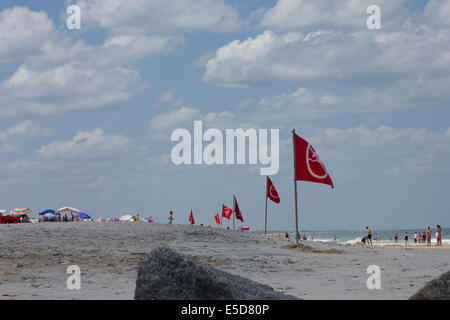 Windy day at Vilano Beach; Rocks, surfing, warning flags; people on background; waves, sand. hot summer - Stock Photo