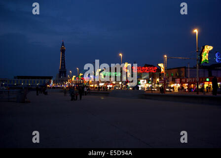 People strolling down the promenade  looking at Blackpool illuminations with the tower lit up in the distance - Stock Photo