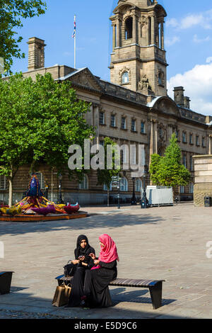 Two young muslim girls in traditional dress sitting in front of the Town Hall, Market Square, Preston, Lancashire, - Stock Photo