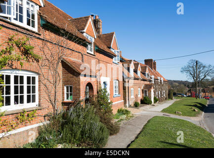 Row of attractive red brick terraced cottages in the village of Great Bedwyn, Wiltshire, UK on a sunny day with - Stock Photo