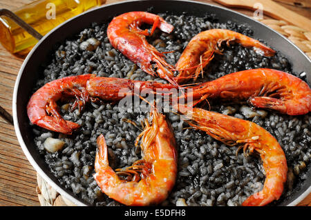 closeup of spanish arroz negro, a typical rice casserole made with squid ink - Stock Photo