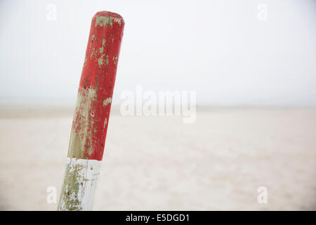Germany, Lower Saxony, East Friesland, Langeoog, red and white wooden stake in front of the beach - Stock Photo