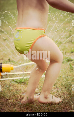 Lttle girl having fun with lawn sprinkler in the garten, partial view - Stock Photo