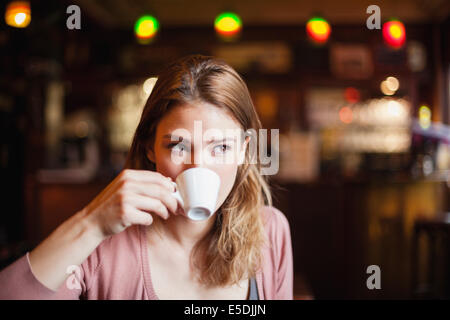 France, Paris, portrait of young woman drinking cup of coffee in a cafe - Stock Photo