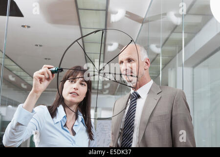 Germany, Munich, Businesswoman in office, drawing chart on glass pane - Stock Photo