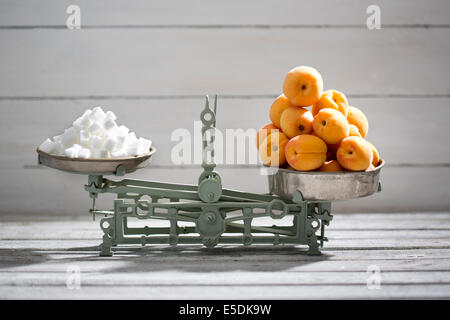 Apricots and sugar cubes on a scale - Stock Photo