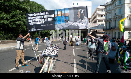After Palestinian protest against Israeli bombing in Gaza men hold up Nelson Mandela freedom banner, London .2014 - Stock Photo