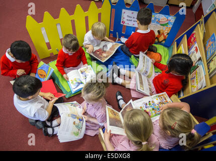 Primary school children reading in a classroom in the UK. - Stock Photo