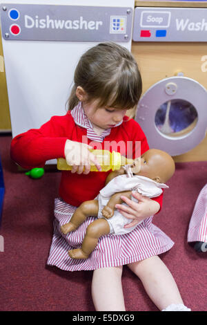 A girl at a UK primary school pretending to feed a baby doll with a bottle - Stock Photo