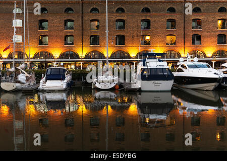 Boats and reflections in St Katharine Docks at sunset. St Katharine Docks, in the London Borough of Tower Hamlets - Stock Photo