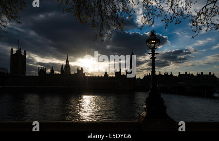Big Ben and the Houses of Parliament viewed in silhouette at sunset from the south bank of the River Thames. - Stock Photo