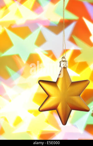 Gold Christmas star close-up over colorful background - Stock Photo