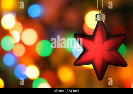 Red Christmas star close-up over colorful background - Stock Photo