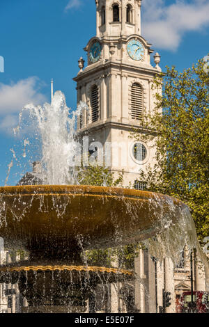 Trafalgar Square's famous water fountains and St Martin in the Fields church, London - Stock Photo