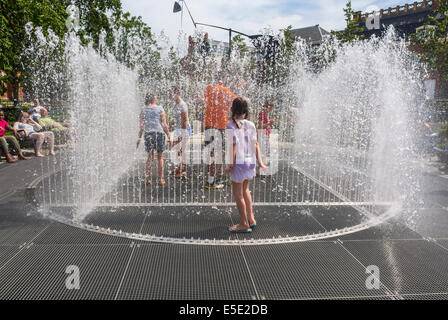 Amsterdam, Holland, Tourist Children Cooling off in Public Garden Fountains during Summer Heat Spell - Stock Photo