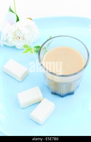 Hot milk coffee and three white chocolates - Stock Photo