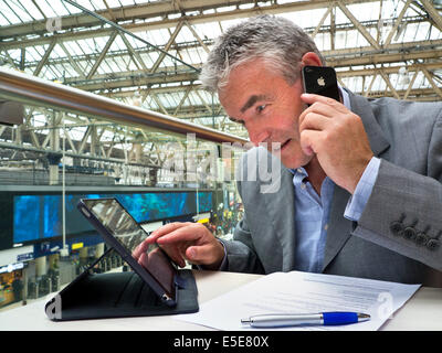 Busy mature businessman seated at cafe table on railway concourse looking at his tablet computer screen and using - Stock Photo