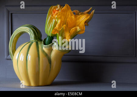 courgettes in courgette style vase on painted kitchen unit - Stock Photo