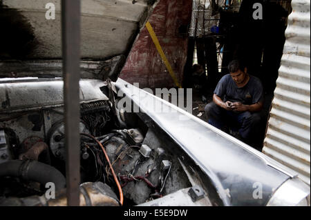 A Cuban mechanic repairs a car in Havana, Cuba. - Stock Photo