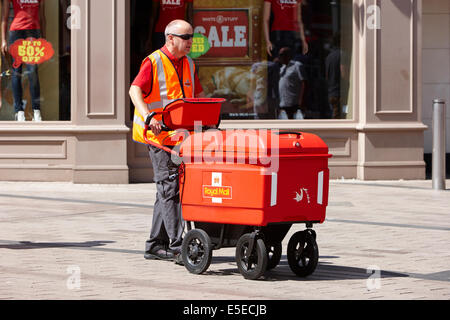 royal mail postman wheeling a cart of mail Belfast city centre - Stock Photo