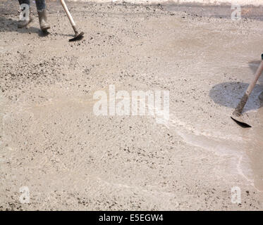 Concrete pouring works during commercial concreting floors; laborer compacting liquid cement into reinforcement - Stock Photo